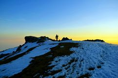 Silhouettes of People reaching at snow covered hill top after treacherous day long trek. People reaching at snow covered hill top after treacherous day long trek Royalty Free Stock Images