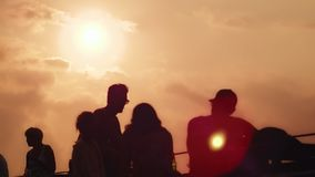 Silhouettes people resting and talking in evening cafe on sunset background stock footage