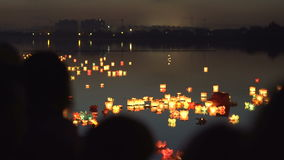 Silhouettes of people on the river bank. People look at the water lanterns. stock video