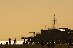 Silhouettes of people at Santa Monica. Santa Monica, Los Angeles, CA, USA - 26th May 2013: Silhouettes of people walking at Santa Monica pier at sunset Royalty Free Stock Photography