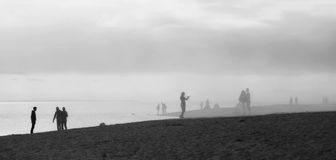Silhouettes of people standing on the shore of the sea bay in th. E fog and taking pictures. Black and white. Panorama royalty free stock image