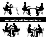 Silhouettes of people at a table Stock Images