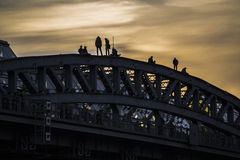 Silhouettes of people on top of the arch bridge Stock Photo