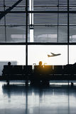 Silhouettes of people waiting at the plane boarding gates. Royalty Free Stock Photos