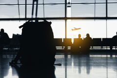 Silhouettes of people waiting at the plane boarding gates. Stock Images
