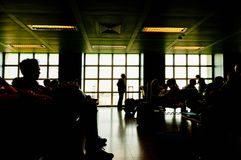 Silhouettes of people waiting at plane boarding gates stock image