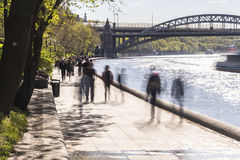 Silhouettes of people walk along the embankment of a city river Stock Images