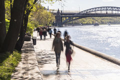 Silhouettes of people walk along the embankment of a city river Royalty Free Stock Photo