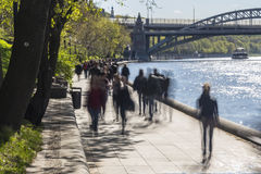 Silhouettes of people walk along the embankment of a city river Royalty Free Stock Images