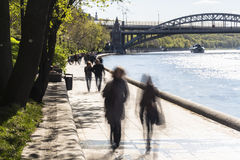 Silhouettes of people walk along the embankment of a city river Royalty Free Stock Photography