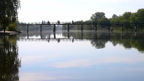 Silhouettes of people walking across the bridge across the river. On the surface of the river the sky with white clouds is mirrored stock video footage