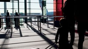 Silhouettes of people walking across sunlit terminal, travel by air, slow motion. Stock footage stock video