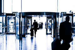Silhouettes of people walking in airport. Royalty Free Stock Photos