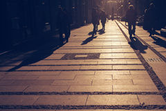 Silhouettes of people walking on city street. And casting shadows on pavement, general public concept for any community related theme Royalty Free Stock Image