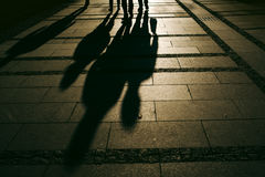 Silhouettes of people walking on city street. And casting shadows on pavement, general public concept for any community related theme Stock Photo