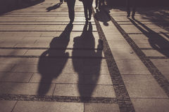 Silhouettes of people walking on city street. And casting shadows on pavement, general public concept for any community related theme Royalty Free Stock Images