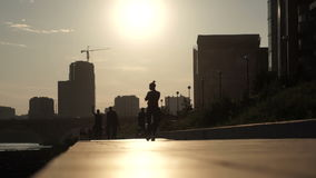 Silhouettes of people walking down the street of the city stock video footage