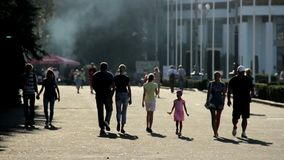 Silhouettes of people walking in park. Street food festival at exhibition center. Stock footage stock video