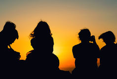 Silhouettes of people watching sunset. Relax concept Stock Photography