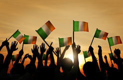 Silhouettes of People Waving the Flag of Ireland Royalty Free Stock Images