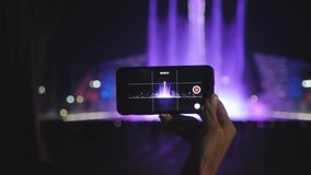 Silhouettes of people who are watching and taking photos the bright color fountain. People take a photo of the light and. Music fountain show stock footage