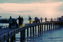 Silhouettes of people on the wooden bridge over the sea, the tropical island,. Toning Stock Photos