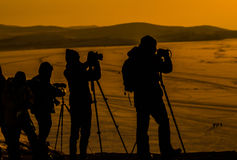 Silhouettes of photographers, with their equipment , shooting a sunset Royalty Free Stock Image