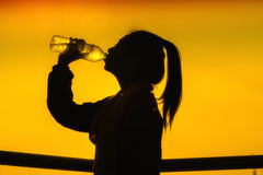 Silhouettes picture of Sporty Asian woman drinking water outdoor Royalty Free Stock Photography
