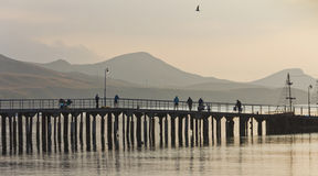 The silhouettes of the pier,boats,fishermen on the background of the mountains and Bay. Stock Photography