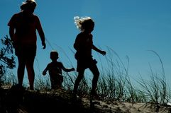 Silhouettes at Play on the Dune. Three silhouetted kids playing on a sand dune Stock Photo