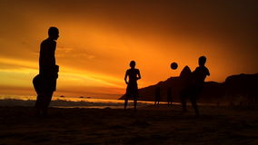 Silhouettes Playing Beach Soccer Rio de Janeiro Brazil. Silhouettes playing football on the beach in front of golden sunset on Ipanema Beach in Rio de Janeiro stock video