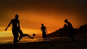 Silhouettes Playing Beach Soccer Rio de Janeiro Brazil. Silhouettes playing soccer on the beach in front of golden sunset on Ipanema Beach in Rio de Janeiro stock video