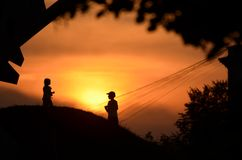 Silhouettes of playing kids. Silhouettes of two kids playing on the hill against orange sky during sunset royalty free stock images