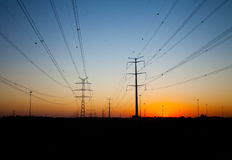 Silhouettes of power transmission line poles at sunset Royalty Free Stock Image