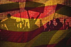 Silhouettes of protesting people against the the flag of Barcelona on the break wall background. Silhouettes of protesting people against the background of the Stock Photography