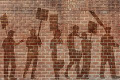 Silhouettes of protesting people against the the flag of Barcelona on the break wall background. Silhouettes of protesting people against the background of the Stock Images