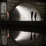 Silhouettes and reflections of tourists under a medival bridge Stock Image