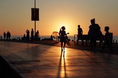 Silhouettes of resting people on sea beach crowdy sunset background royalty free stock photo