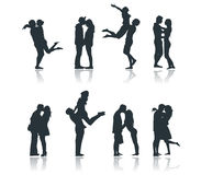 Silhouettes of romantic couples loving kissing flirting boyfriend girlfriend Stock Images
