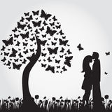 Silhouettes of romantic tree from butterflies and lovers. Royalty Free Stock Images