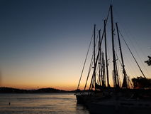 Silhouettes of sail poles at sun set royalty free stock photography