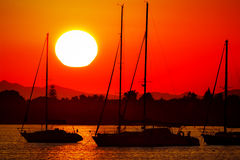 Silhouettes of sailing boats at red and orange sunset Royalty Free Stock Photos