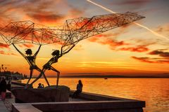Silhouettes sculpture of fishers on lake embankment at sunset Stock Photo