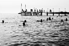 Silhouettes of a sea pier. Silhouettes of having a rest people. It is black a white photo of a sea pier and having a rest people Stock Photography