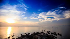Silhouettes in Sea by Rocks Boats Sun from Behind Clouds stock video footage