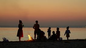Silhouettes on the seashore. Big family have a rest by the sea near a fire. People have a rest near a fire after a. On this video you can see as the close-knit stock video footage