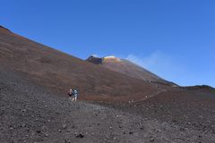 Silhouettes of people standing on a slope of Etna - the highest active volcano in Europe Royalty Free Stock Image