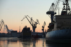 Silhouettes of ships and portal cranes Stock Image
