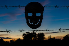 Silhouettes of Skull and Barbed wire on sunset background Royalty Free Stock Images