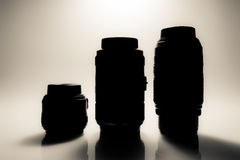 Silhouettes of SLR camera lenses close-up with reflection. Old style vintage photo. Stock Photography